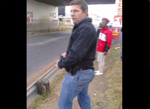 A screenshot of a man carrying a gun.