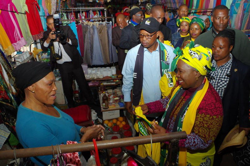 Nkosazana Dlamini-Zuma (right) chats to a trader at Durban's Mansell Road Market during campaigning for the country's upcoming local government elections before handing the trader a shirt. Looking on is the ANC's provincial secretary Super Zuma (light blue shirt and black cap). Picture: Giordano Stolley/ANA