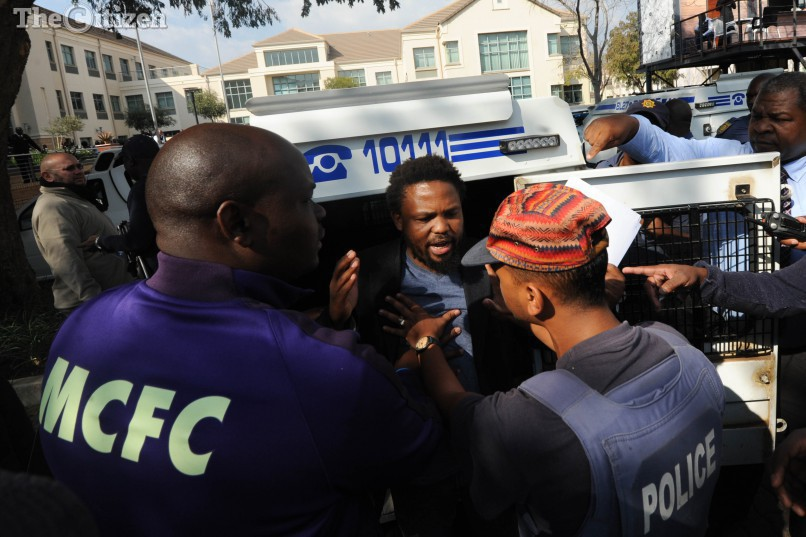 Police detain the leader of the Black First, Land First movement, Andile Mngxitama,18 July 2016, after they entered the public protector's office in Pretoria. Members of the political party stormed past the security in the building in an attempt to meet the public protector who was out doing charity work for Nelson Mandela Day. They are calling for answers into an investigation over R26 billion allegedly stolen from the Reserve Bank pre-1994. Picture: Alaister Russell