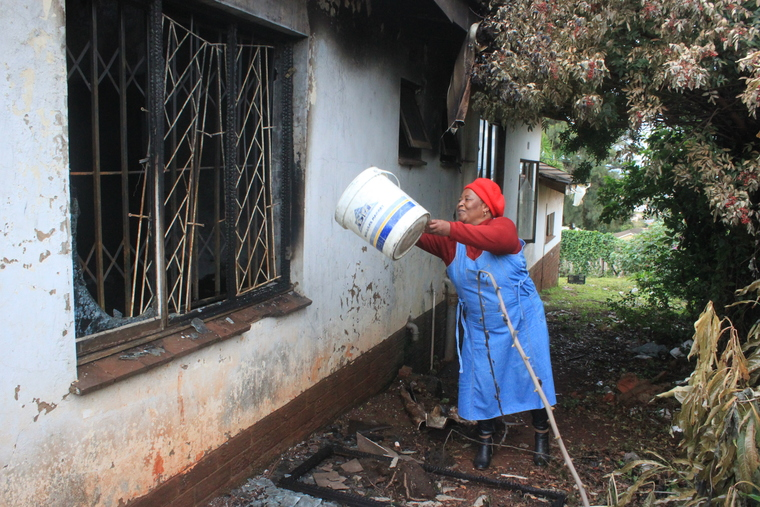 Thandiwe Mchunu attempting to put out the inferno with a bucket.