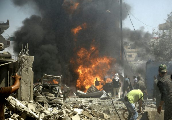 AFP/File / Delil Souleiman<br />Residents gather at the site of a bomb attack in Syria's northeastern city of Qamishli on July 27, 2016, claimed by the Islamic State group