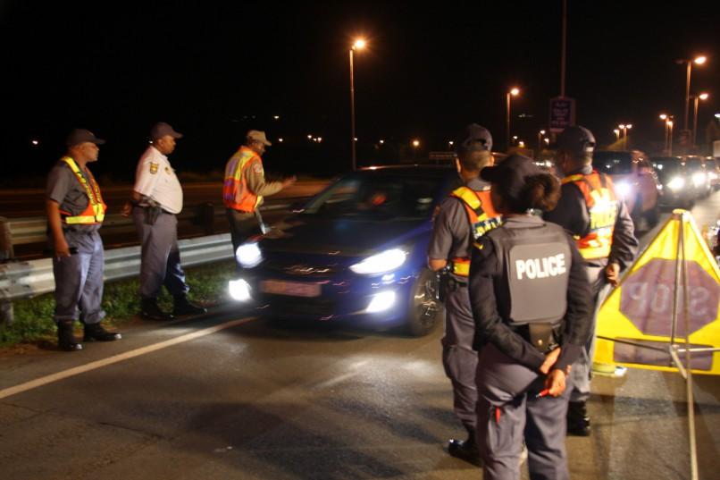 A drunk driver feigns sleep at a roadblock.