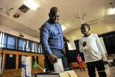 Solly Msimanga and his son dropping his vote in the ballot box at Capital Park Primary School voting station, 3 August 2016, Pretoria. Picture: Jacques Nelles