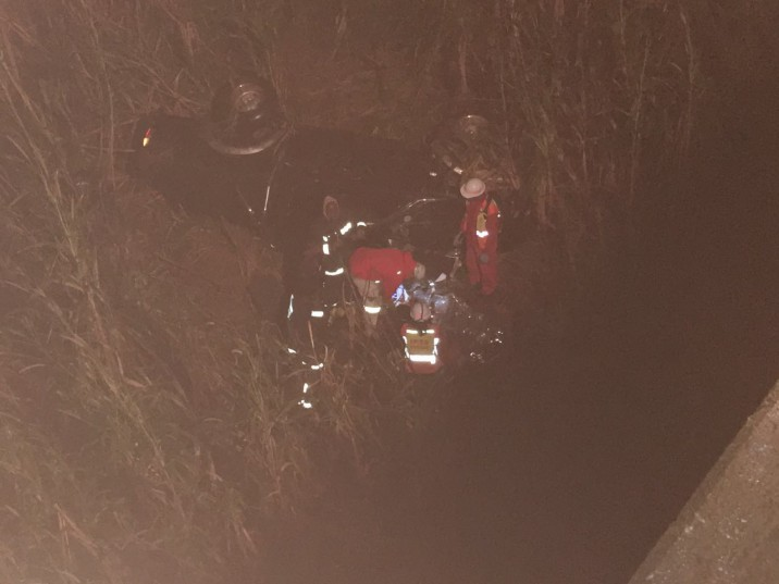 Fire department members attempting to rescue the driver from the wrecked car below Maidstone bridge. Photo: IPSS Medical Rescue
