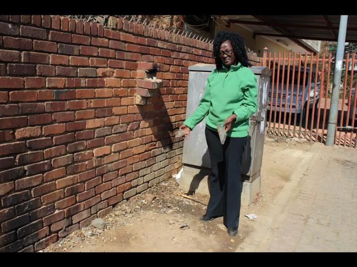 Social worker Anastatia Mosethla holds broken bottles found outside Tshwane Child Welfare in Mamelodi West.