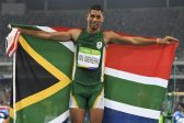 RIO DE JANEIRO, BRAZIL - AUGUST 14: Wayde van Niekerk of South Africa holds up the South African national flag after he won the mens 400m final in a new world record of 43.03 seconds during the evening session on Day 9 Athletics of the 2016 Rio Olympics at Olympic Stadium on August 14, 2016 in Rio de Janeiro, Brazil. (Photo by Roger Sedres/Gallo Images)
