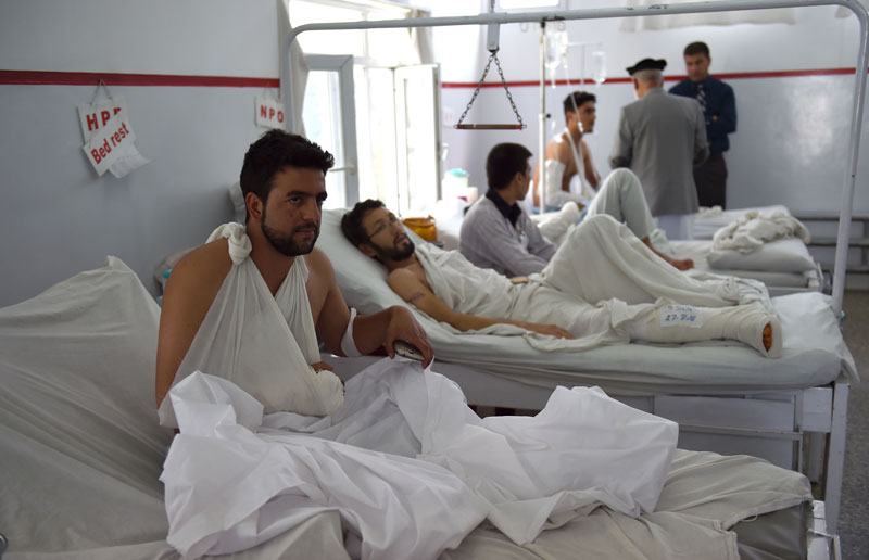 A wounded Afghan police man (L) looks on as he receives treatment, following the militants' raid that targeted the elite American University of Afghanistan, at the Italian aid organization hospital in Kabul on August 25, 2016.   At least 12 people were killed after militants stormed the American University of Afghanistan in Kabul, officials said, in a nearly 10-hour raid that prompted anguished pleas for help from trapped students. / AFP / WAKIL KOHSAR