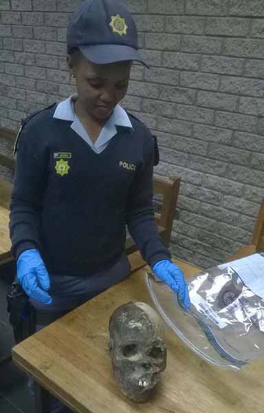 Constable Thembelihle Madlala with the human head recovered from two suspects who were arrested when they tried to sell it to traditional healers. PHOTO: Berea Mail.