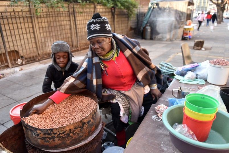 A woman roasts peanuts to sell to the long queues of voters outside Joubert Park in the JHB CBD, 3 August 2016. Picture: Tracy Lee Stark