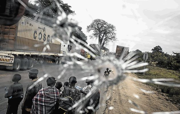 HELL RUN: Street vendors are seen through a bullet hole in a bus windscreen alongside the Mozambican Main North South road at Nhamapaza in Gorongosa, where convoys are escorted by the army after increased skirmishes between Frelimo troops and Renamo forces. Image by: JOHN WESSELS/AFP