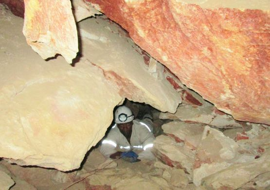 Mine Rescuer climbs through broken ground on mission in abandoned mine.
