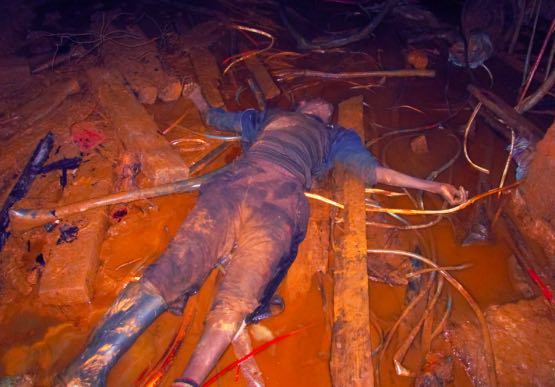 A deceased miner killed by a rival faction underground.