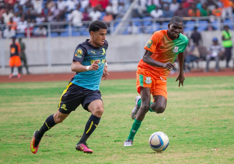Keagan Dolly of Mamelodi Sundowns dribbles past Misheck Chaila of Zesco United