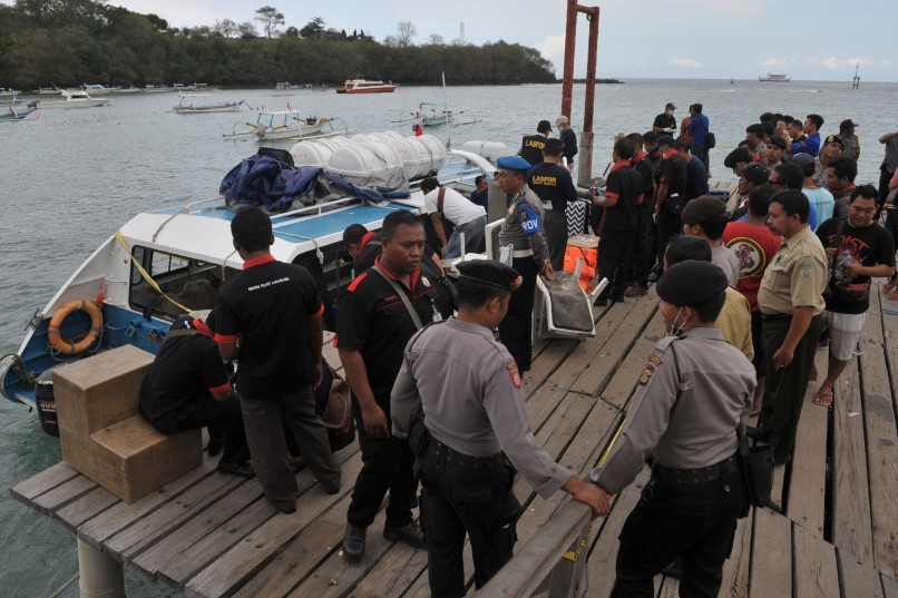 Police conduct investigations on a speedboat following an explosion on the vessel in Karang Asem, Indonesia's resort island of Bali, on September 15, 2016.   An explosion on a speedboat in Bali left one foreign woman dead and 19 other tourists injured on September 15, police on the Indonesian holiday island said. / AFP / STR