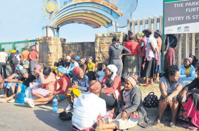 Families outside the George Harrison Park in Langlaagte, waiting for news of a group of illegally operating miners trapped underground. Picture: Michel Bega