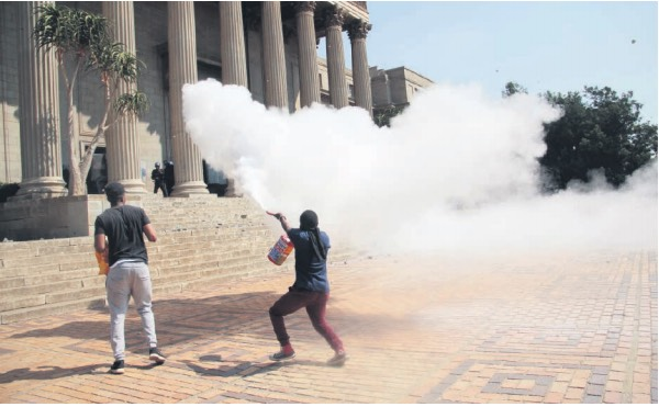 Wits students stone the Great Hall and clash with security police yesterday during the #FeesMustFall protest. Picture: Rosetta Msimango