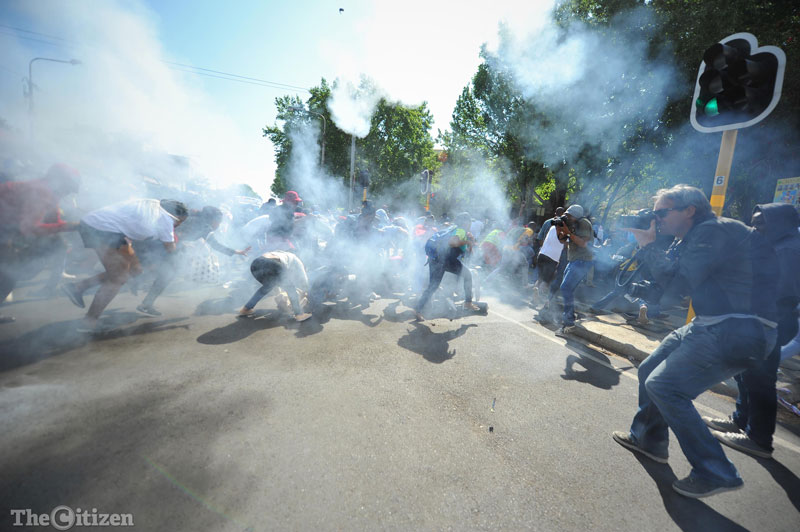 Students run away from a stun grenade thrown by the SAPS during a protest outside Wits University, 21 September 2016. South African police fired stun grenades and rubber bullets to disperse the students protesting for the free education and the decolonisation of education. Picture: Michel Bega