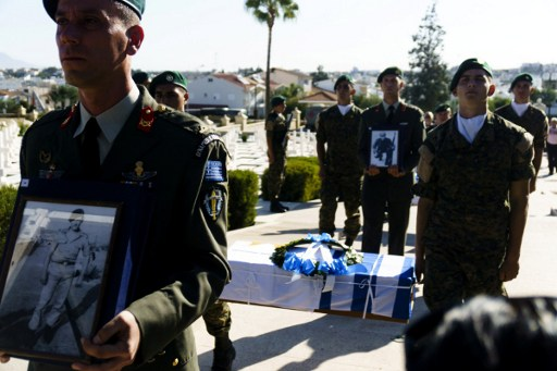Members of Cyprus armed forces carry coffins during a ceremony to hand over the remains of 16 Greek commandos, who were killed by friendly fire during Turkey's 1974 invasion of Cyprus, on October 4, 2016 at a military cemetery outside the capital Nicosia.  The soldiers were on board a French-built Noratlas transport aircraft that was headed to Nicosia airport to reinforce the Greek Cypriot National Guard when it was mistaken for a Turkish bomber and shot down. Cypriot President Nicos Anastasiades apologised both for the anti-aircraft fire that killed the soldiers and for the decades of delay in returning their bodies. / AFP PHOTO / Iakovos Hatzistavrou