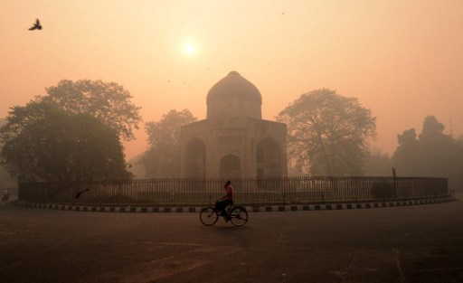 An Indian cyclist rides along a street as smog envelops a monument in New Delhi on October 31, 2016, the day after the Diwali festival. New Delhi was shrouded in a thick blanket of toxic smog a day after millions of Indians lit firecrackers to mark the Diwali festival, causing the air pollution to hit