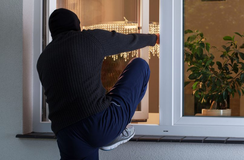 Burglar climbing out of a window. Photo: Stock image