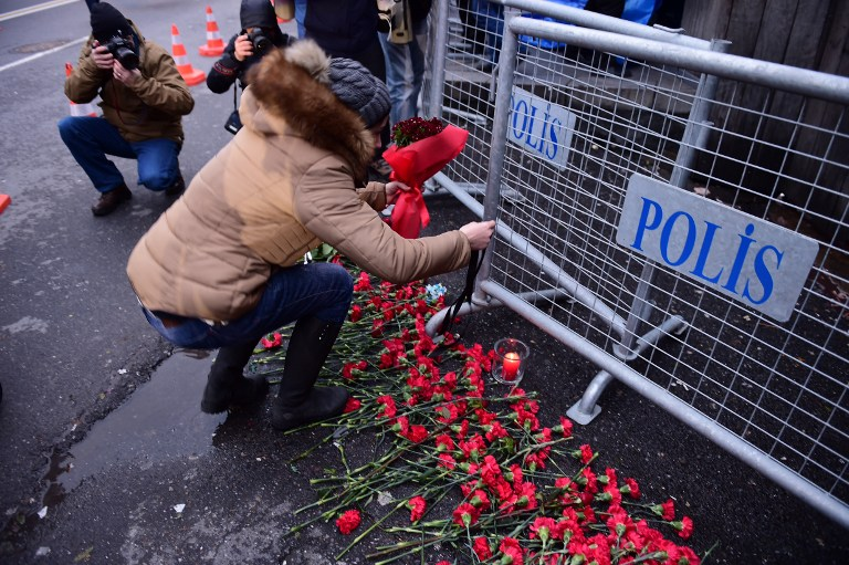 People lay flowers in front of the Reina night on January 1, 2017 in Istanbul, after a gunman killed 39 people, including many foreigners, in a rampage at an upmarket nightclub in Istanbul where revellers were celebrating the New Year. The shooting spree at the waterside Reina nightclub was unleashed when 2017 in Turkey was just 75 minutes old, after a year of unprecedented bloodshed that saw hundreds of people die in strikes blamed on jihadists and Kurdish militants and a bloody failed coup. / AFP PHOTO / YASIN AKGUL