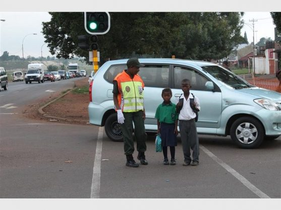 Joyce Mariri from Slovo Park, one of the EMPD peace corps officials, helps two Payneville Primary School children cross an intersection in Bakerton. Picture: Springs Advertiser