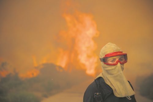 epa05710702 A female firefighter battles a blaze during a fire spreading rapidly through residential areas in the mountainous suburb of Simonstown in Cape Town, South Africa, 11 January 2017. Hundereds of residents are being evacuated as the fire fanned by strong north westerly winds started in Ocean View ripped through Glencairn heading towards Simonstown according to eye witness reports at the scene.  EPA/NIC BOTHMA