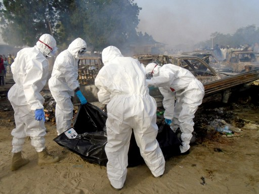 Forensics cover a dead body and clear the scene of a blast in Maiduguri on February 17, 2017.  As many as seven suicide bombers, including six women, tried to attack the northeast Nigerian city of Maiduguri but only succeeded in blowing themselves up, emergency services officials said on February 17, 2017. / AFP PHOTO / STRINGER