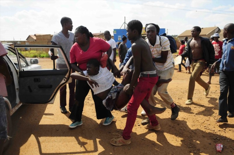 A mob carries an injured boy to a car during service delivery protest on April 11, 2016 in Orange Farm, South Africa. The 15-year-old boy was allegedly shot by a Somali international after a group of protesters tried to loot his shop. Picture: Gallo Images