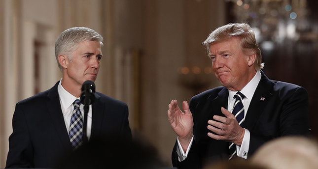President Donald Trump applauds as he stands with Judge Neil Gorsuch.