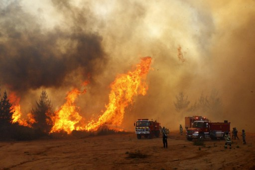 Picture released on March 12, 2017 by Aton Chile shows firefighters working to put out a forest fire in Valparaiso. Chilean authorities decreed red alert in Valparaiso and Vina del Mar for several forest fires. / AFP PHOTO / ATON CHILE / Raul ZAMORA / Chile OUT