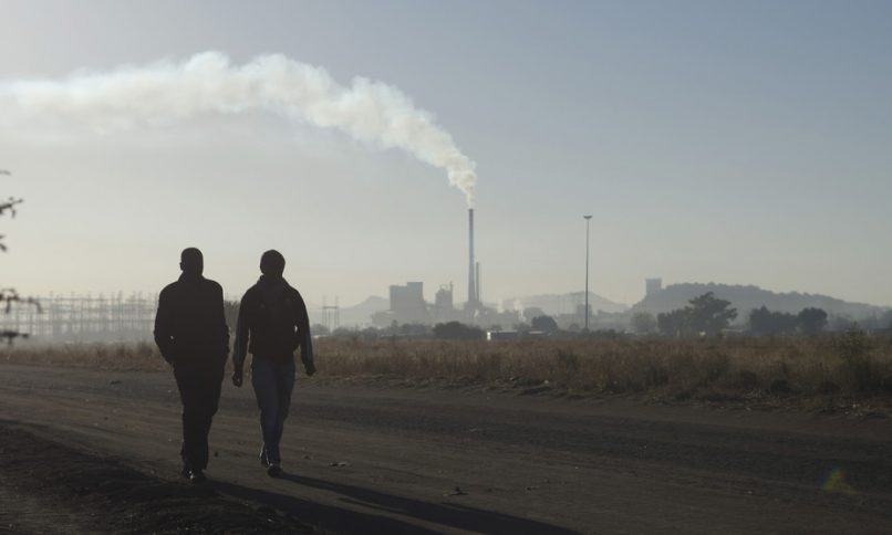 Workers walk past a Lonmin Marikana platinum mine, a site that represents industrial strife in South Africa. Reuters/Skyler Reid