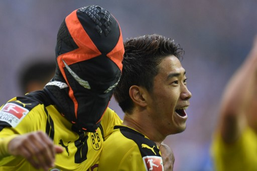 Dortmund's Gabonese striker Pierre-Emerick Aubameyang (L) wears a mask as he celebrates with his teammate Dortmund's Japanese midfielder Shinji Kagawa after scoring the 0-1 during the German first division Bundesliga football match between FC Schalke 04 and Borussia Dortmund in Gelsenkirchen, western Germany, on April 1, 2017. / AFP PHOTO / PATRIK STOLLARZ / RESTRICTIONS: DURING MATCH TIME: DFL RULES TO LIMIT THE ONLINE USAGE TO 15 PICTURES PER MATCH AND FORBID IMAGE SEQUENCES TO SIMULATE VIDEO. == RESTRICTED TO EDITORIAL USE == FOR FURTHER QUERIES PLEASE CONTACT DFL DIRECTLY AT + 49 69 650050