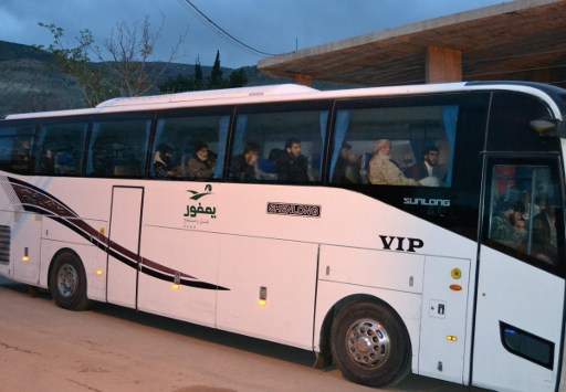A bus carrying Syrian evacuees is seen in the rebel-held town of Madaya leaving under a deal brokered by opposition backer Qatar and regime ally Iran, on April 14, 2017.  All 16,000 residents of Fuaa and Kafraya are expected to leave, heading to government-held Aleppo, the coastal province of Latakia or Damascus. Civilian residents of Madaya and Zabadani will reportedly be allowed to remain if they choose. Those who opt to leave with the fighters will head to rebel-held territory in Idlib. / AFP PHOTO / STRINGER