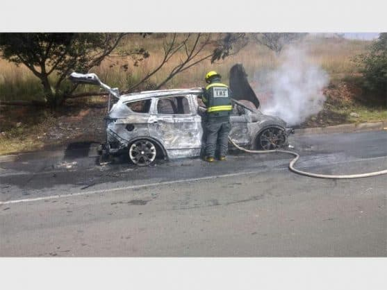 A firemen at the burnt-out wreck of the Ford Kuga on CR Swart Road. (Photo: Supplied)