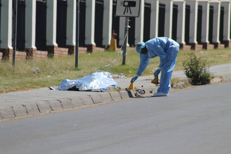 A police forensic expert places a marker next to the body.