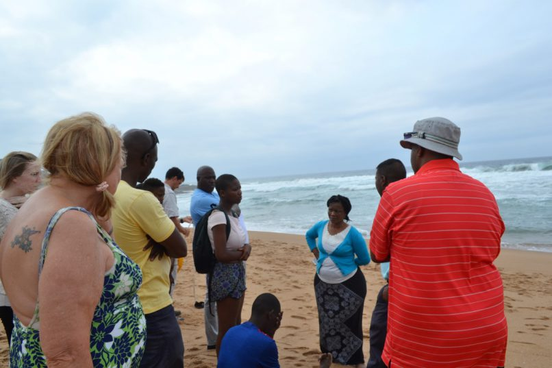 Beach goers and emergency service gather at beach to comfort the man whose friend had drowned.