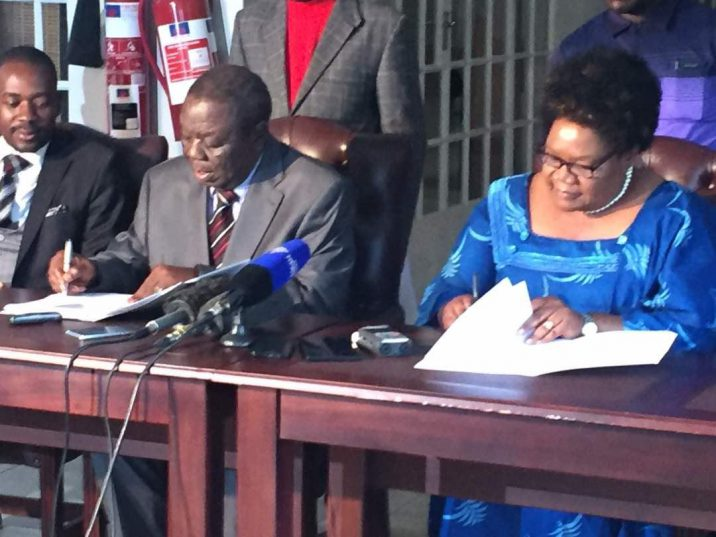 MDC-T leader Morgan Tsvangirai (centre) and NPP leader Joice Mujuru (right) sign the pre-election coalition MoU while MDC-T vice-president Nelson Chamisa looks on at Tsvangirai's residence in the capital Wednesday.