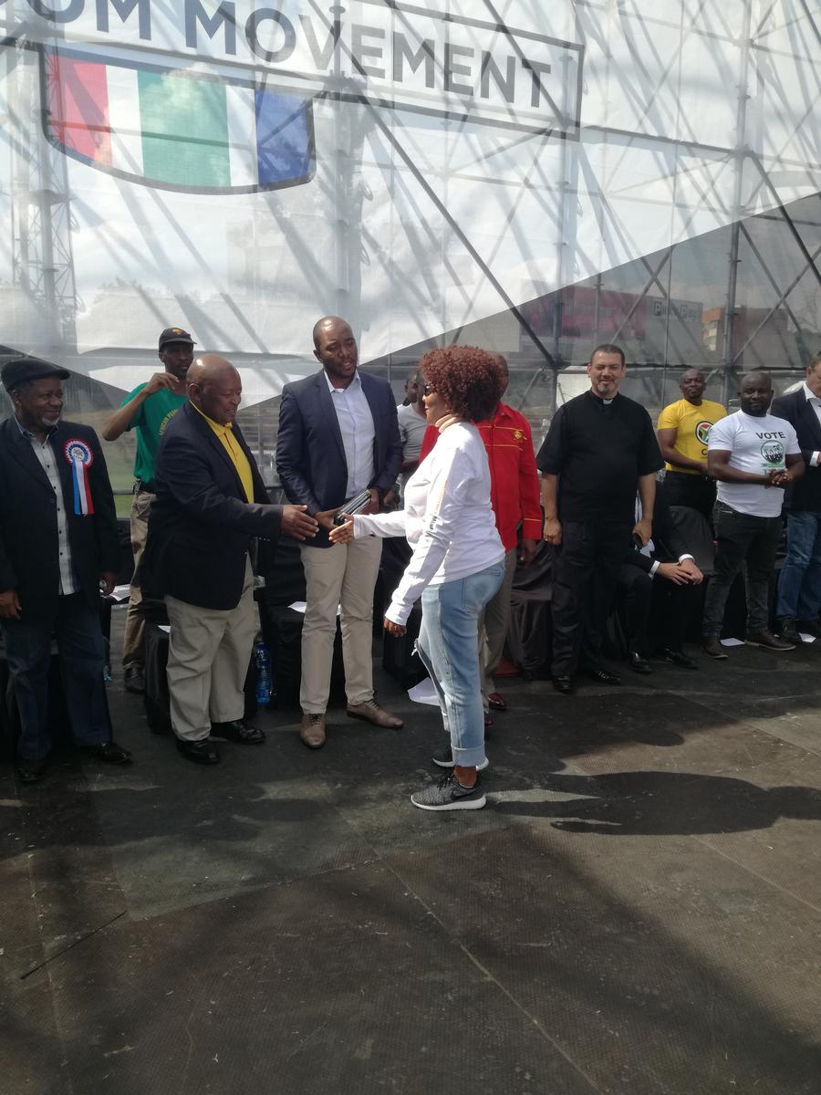 Ndileka Mandela shaking hands with cope leader Mosiua Lekota after her speech.