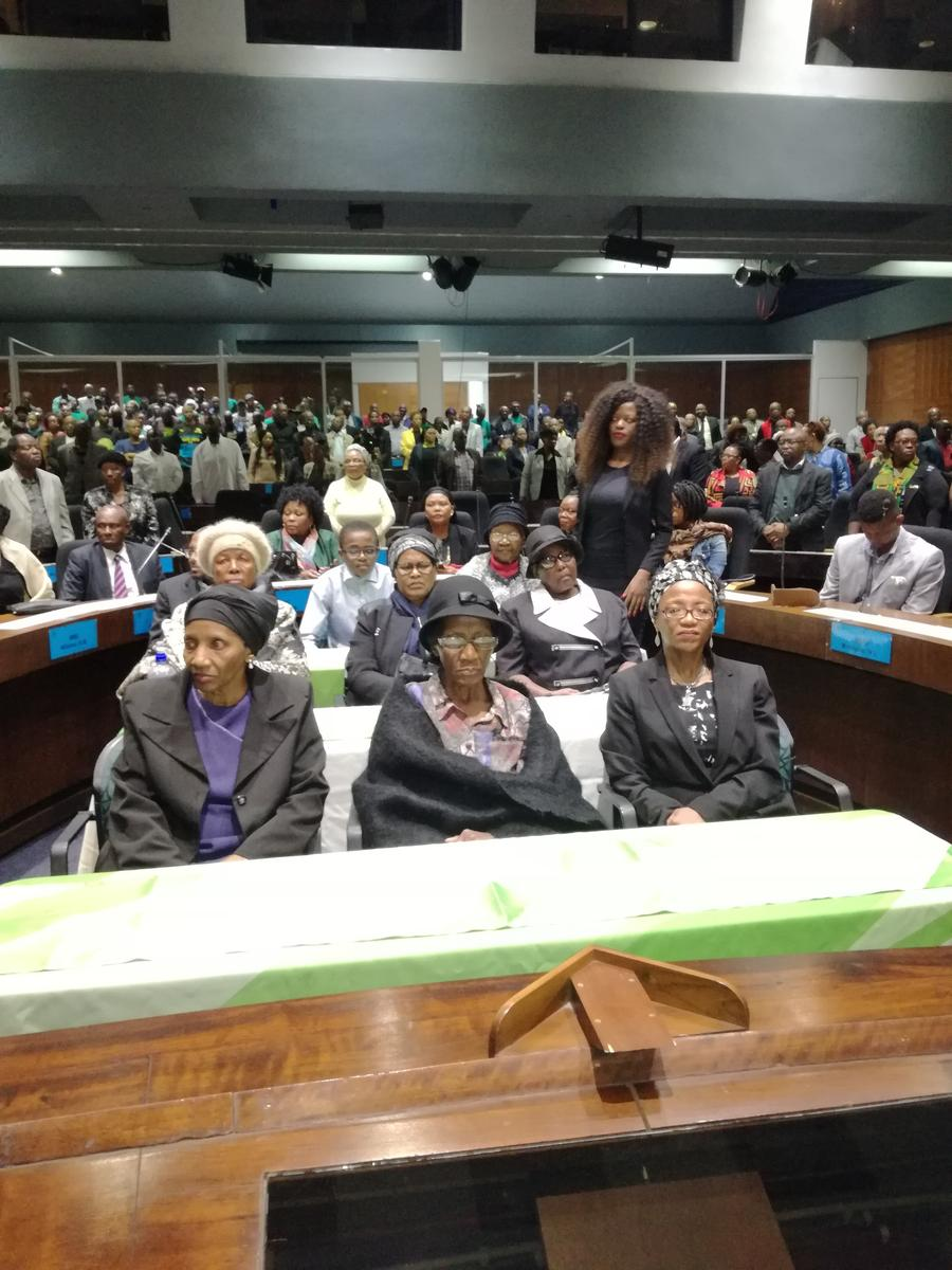 Philip Kgosana's wife dressed in a black hat and shawl while flanked by family members.