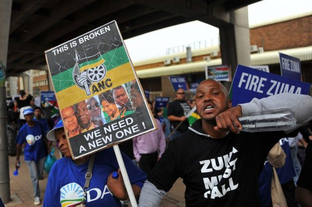 Protesters hold placards as they join a mass protest calling for President Jacob Zuma to step down, 7 April 2017, in Johannesburg. President Zuma is facing growing backlash against his recent government reshuffle and axing of the finance minister. Picture: Michel Bega
