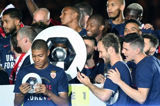 """Monaco's French forward Kylian Mbappe Lottin (L) celebrates at the end of their last French L1 football match Monaco (ASM) vs St Etienne (ASSE)  on May 17, 2017 at the """"Louis II Stadium"""" in Monaco. Monaco on May 17 won their first French league title in 17 years.  / AFP PHOTO / BORIS HORVAT"""