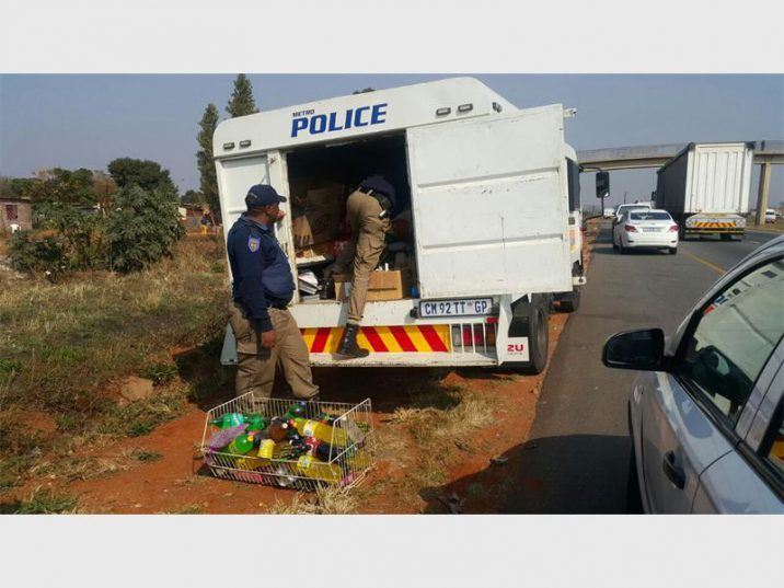 NO-HOLDS-BARRED: Metro Police load stolen goods recovered following looting in Nancefield into truck.