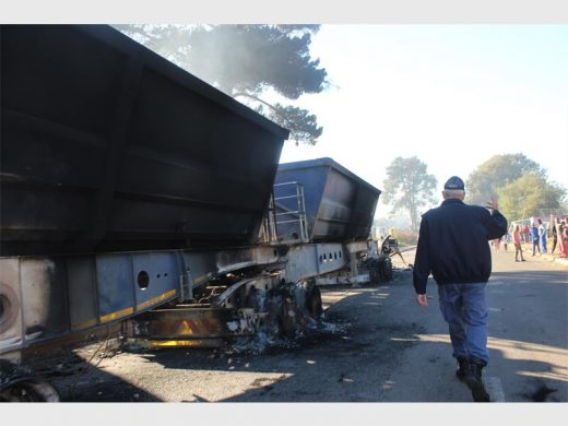 A colonel from the Roodepoort Police walking past the burnt out truck, on his way to speak to a group of angry residents. Photo: Sonwabile Antonie