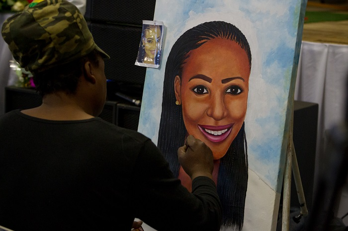 A painter works on a likeness of Karabo Mokoena during her funeral service in the Diepkloof Community Hall in Soweto on 19 May 2017.  Mokoena was killed and burnt, allegedly by her boyfriend, in a murder that shocked the country and catalysed debate around gender based violence. Picture: Yeshiel Panchia