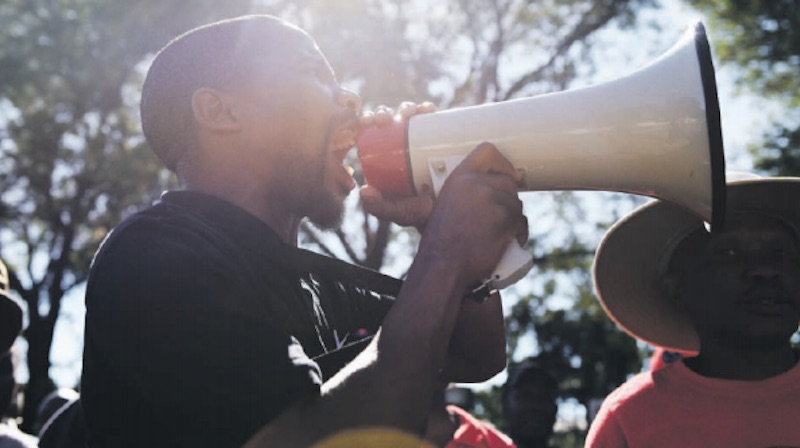 MAKING THEIR VOICE HEARD. A Nehawu member addresses strikers outside the University of Pretoria's main campus in Hatfield yesterday following failed salary negotiations with varsity management. Picture: Refilwe Modise