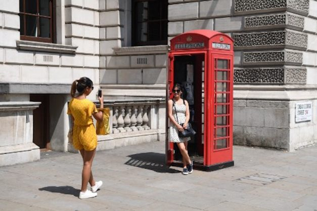 Tourists pose for a photograph in a Telephone Box in the hot weather in central London on June 21, 2017. Europe sizzled under a continent-wide heatwave on June 21, with London bracing for Britain's hottest June day since 1976 as Portugal struggled to stamp out deadly forest fires. / AFP PHOTO / Paul ELLIS