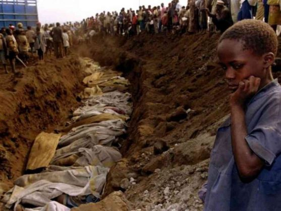 File photo of a Rwandan refugee girl staring at a mass grave where dozens of bodies