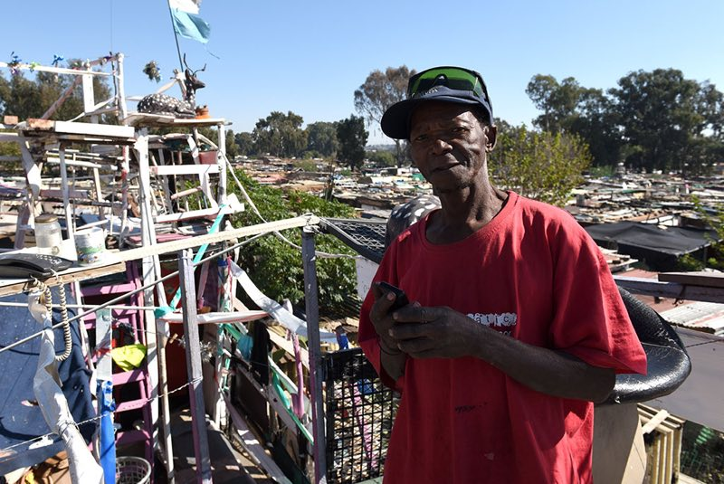 Johannes stands on the third floor of his home where you can take in a view of the surrounding informal settlement.