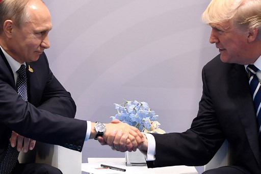US President Donald Trump and Russia's President Vladimir Putin shake hands during a meeting on the sidelines of the G20 Summit in Hamburg, Germany, on July 7, 2017. / AFP PHOTO / SAUL LOEB